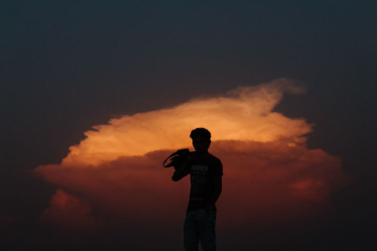 Man standing against sky during sunset