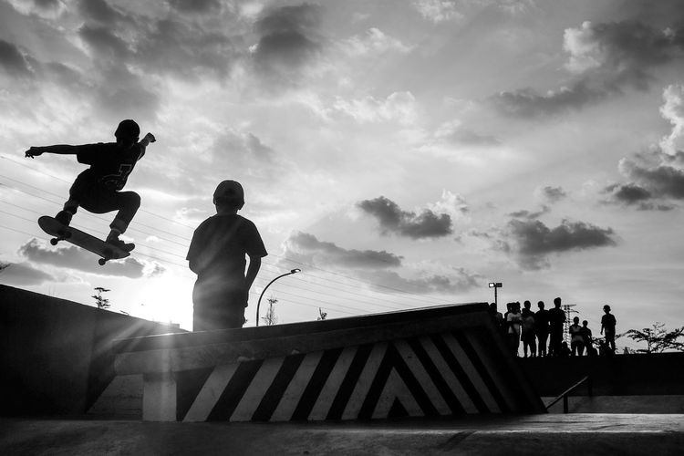 Low angle view of boy skateboarding at skateboard park against sky on sunny day