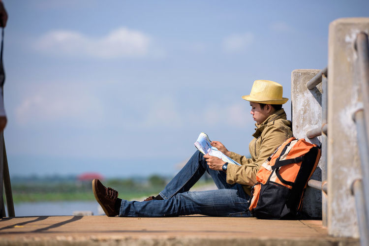 Hiker reading map while sitting on pier against sky