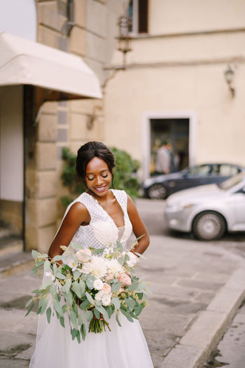 Smiling bride holding bouquet while standing on road