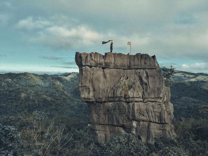 Mid distance on man standing on rock formation against sky