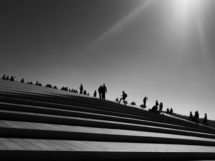 Low angle view of people on steps against sky