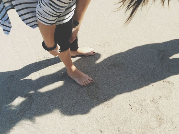 Low section of woman folding leggings while bending at beach