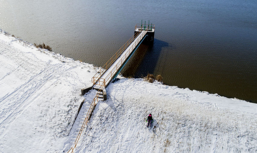 Winter sets in around the Carbondale water reservoir that sits outside the city while a child sleds down an embankment on the man made structure. Water High Angle View Day Nature Built Structure Motion Real People Architecture Outdoors Dam Beauty In Nature People Men Sea Scenics - Nature Sport Hydroelectric Power Flowing Water Flowing Carbondale, Illinois Southern Illinois  Sledding Fun Drone  Aerial View
