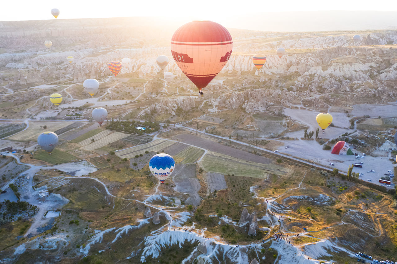 air vehicle, balloon, hot air balloon, transportation, mode of transportation, mid-air, flying, nature, day, ballooning festival, travel, adventure, no people, high angle view, landscape, outdoors, environment, sky, sunlight, airplane