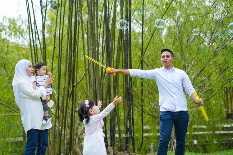 Playful family spending time together at park. Group Of People Men Standing Togetherness Plant Three Quarter Length Tree Young Adult Casual Clothing Human Arm Nature Limb Adult Day Young Men Holding People Human Limb Young Women Human Body Part Body Part Outdoors Arms Raised Positive Emotion