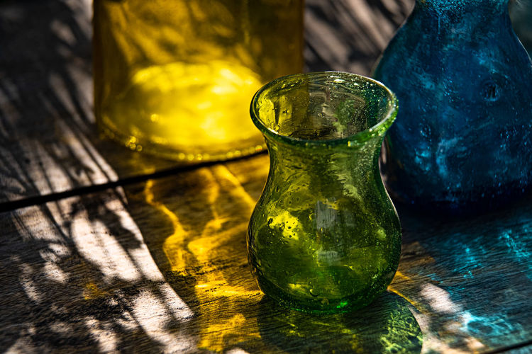 Multi colored vases on a wooden table outdoors in light and shadow