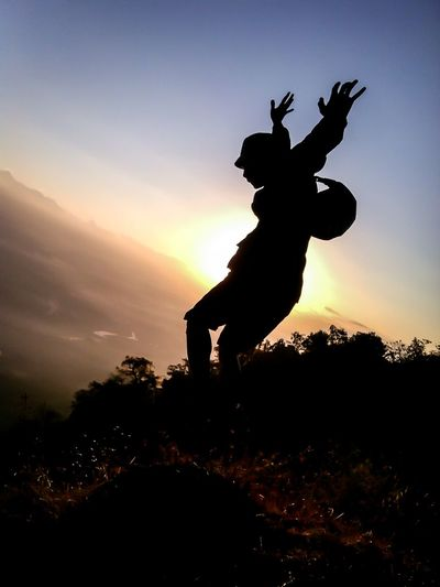 Silhouette person jumping on tree against sky during sunset