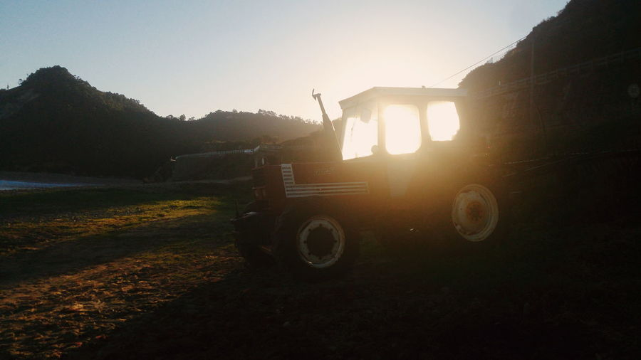 Tractor on field at sunset