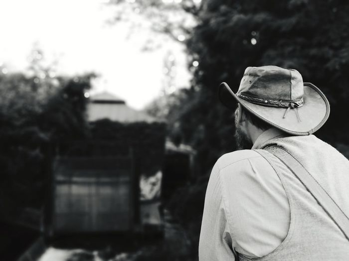 Rear view of man wearing hat while standing against sky