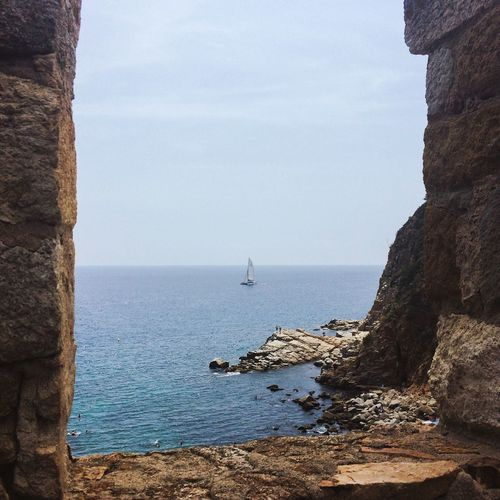 Sailboat In Sea Against Sky Seen From Stone Window At Tossa De Mar
