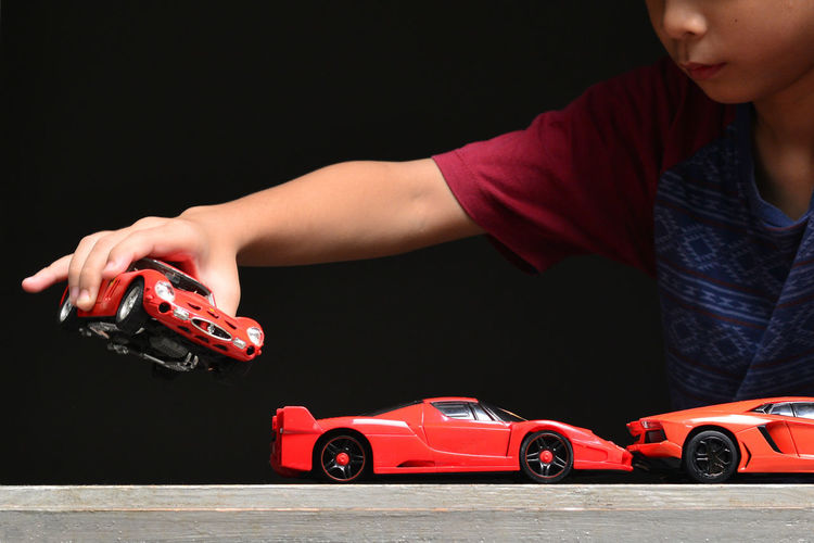 Midsection of boy playing with toy cars against black background