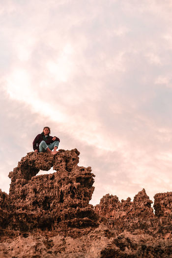 Low angle view of young man sitting on rock against sky