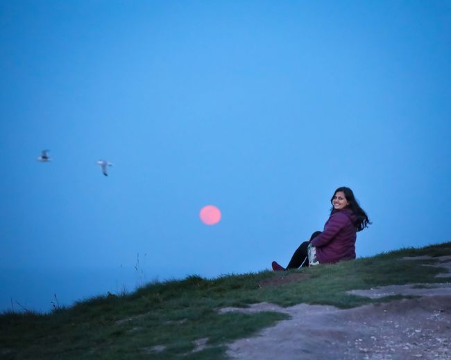 Woman on field against clear blue sky