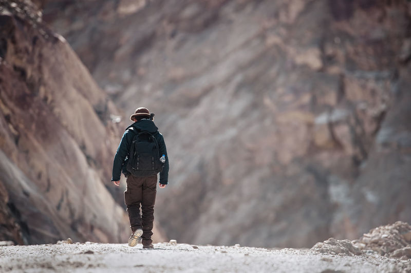 A man walking in the mountains. India Travel Trekking Activity Adventure Backpack Full Length Hiking Leisure Activity Lifestyles Mountain Nature One Person Outdoors Real People Rear View Rock Rock - Object Trek Warm Clothing