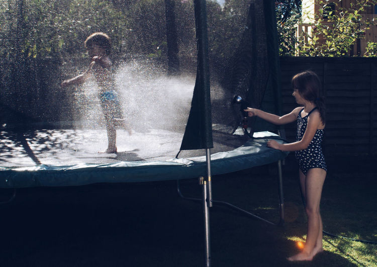 Girl spraying water on her brother standing on trampoline in backyard