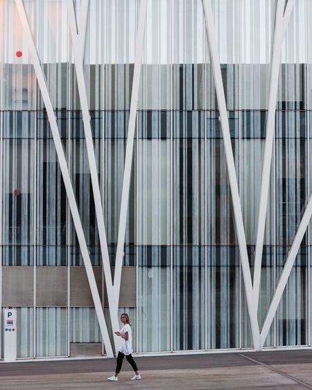 Woman walking by modern office building