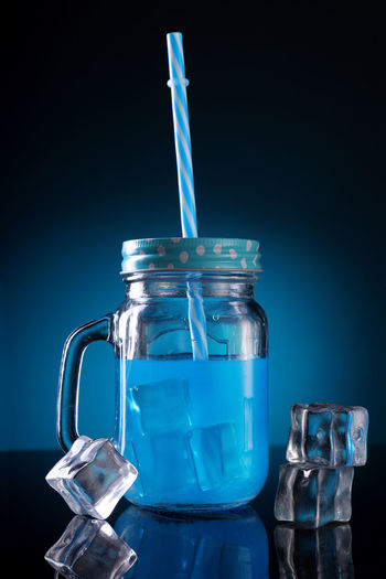 Close-up of glass jar on table against blue background