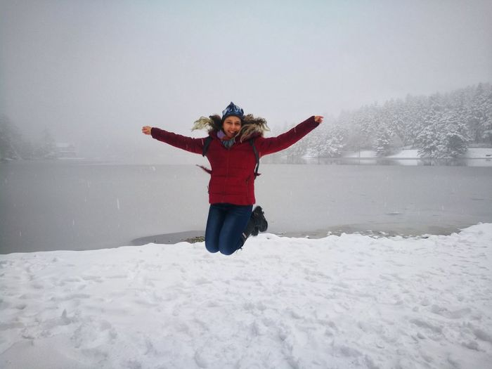Full length of smiling young woman jumping over snow against sky