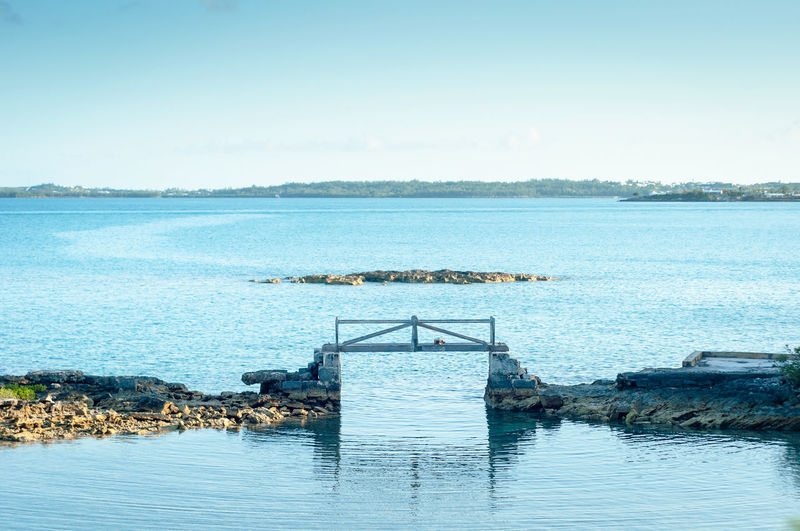Old wood bridge connecting two portions of land at bermuda Island. Atlantic Ocean Beauty In Nature Bermudas Bridge Clear Sky Day Decay Horizon Over Water Nature No People Old Outdoors Rustic Rustic Style Scenics Sea Sea Shore Sky Symetry Tranquility Water Water Reflections Waterfront