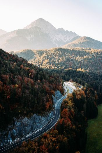 Aerial View Of Road Amidst Trees Against Mountains During Autumn