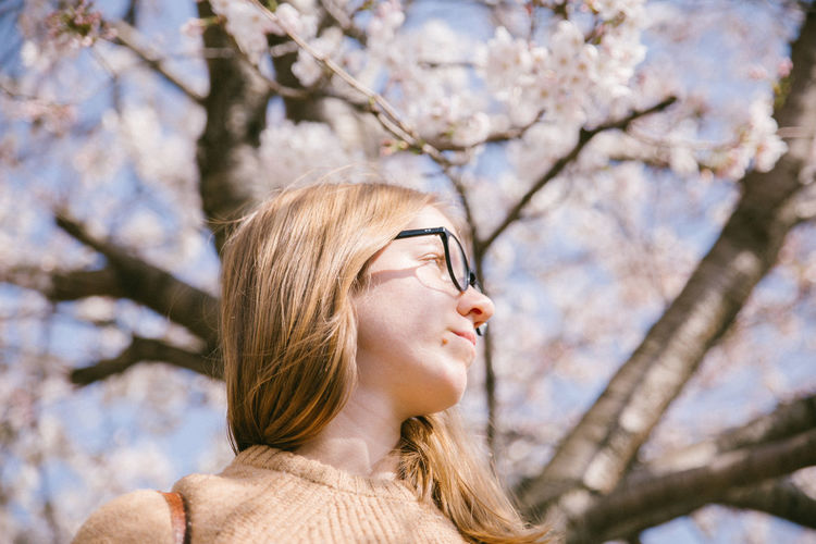 Low angle view of woman against cherry blossom tree