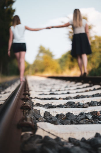 Rear view of woman on railroad tracks against sky