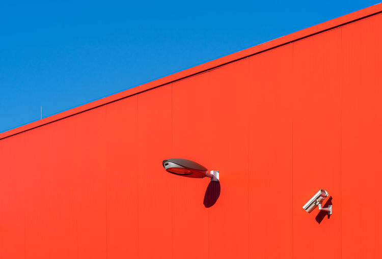 Low angle view of orange wall against clear blue sky