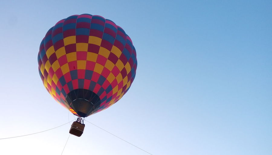 Low angle view of hot air balloon against clear blue sky