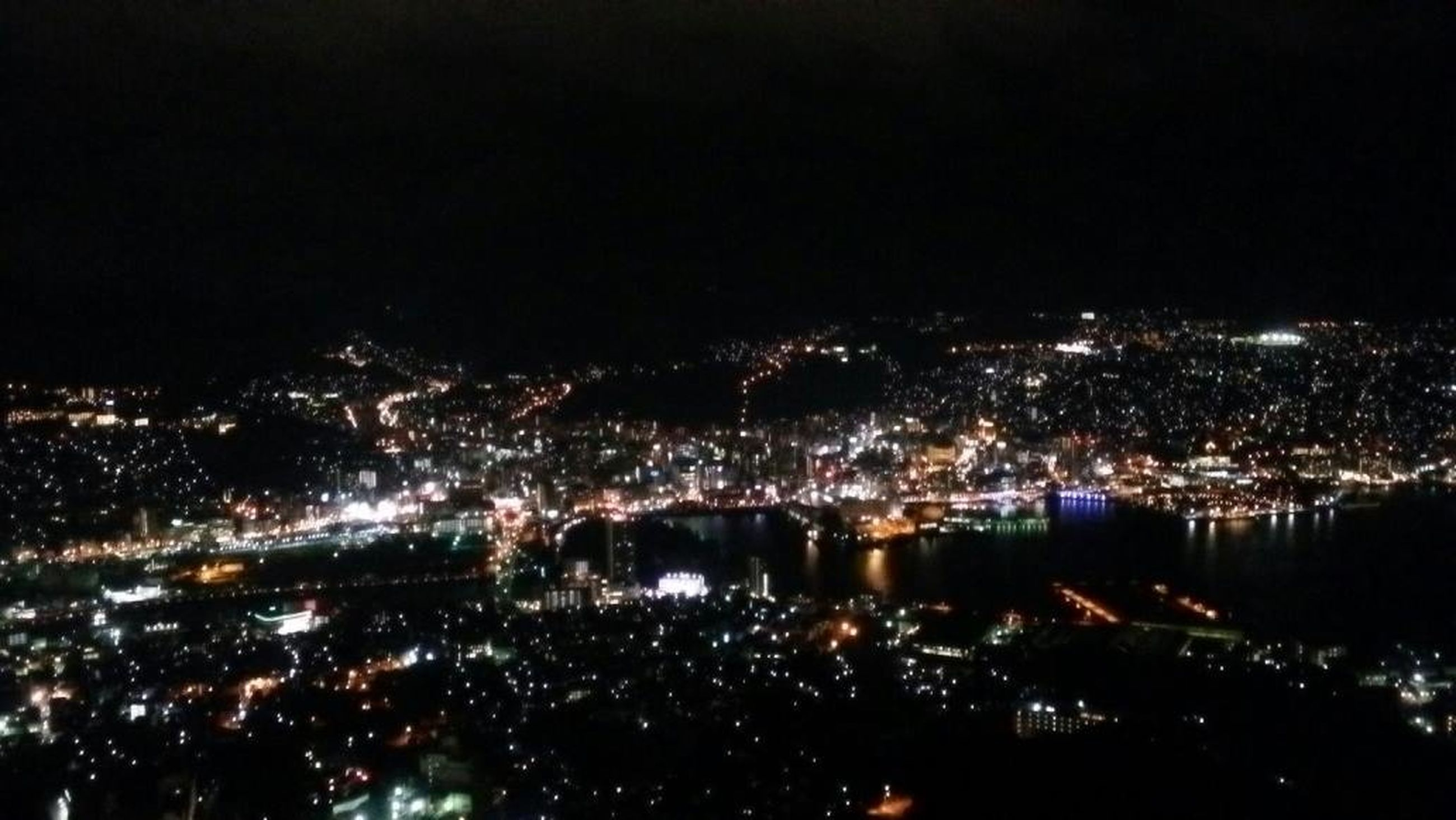 illuminated, night, cityscape, city, crowded, architecture, built structure, high angle view, aerial view, building exterior, water, river, residential district, city life, sky, copy space, clear sky, residential building, outdoors, residential structure