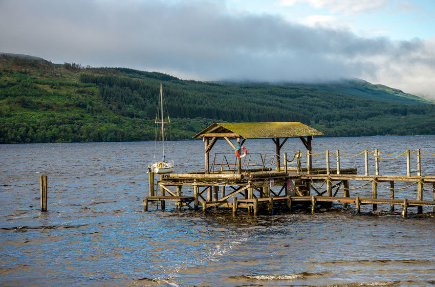 A wooden jetty with a life buoy at Loch Tay, central Scotland Boat Station Family Good Weather Hills Holiday Loch Tay Pier Scotland Tourist Attraction  Trees Calm Water Cloud Sky Forest Highlands Jetty Killin  Lake View Lakeshore Landscape Sailing Boat Summer Travel Destinations Vacation Wooden Yacht