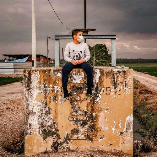 Full length of teenage boy sitting on water against sky