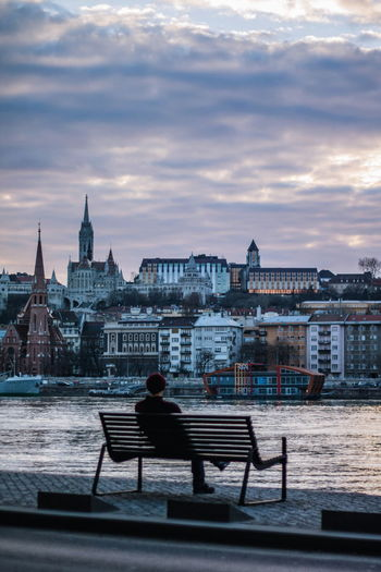 Rear view of man sitting on bench in city against sky during sunset
