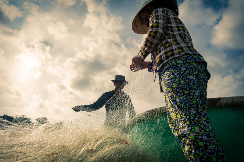 The daily activities in a fishing village in Mui Ne, Vietnam. Real People Sky Water Men Cloud - Sky Leisure Activity Nature Motion Two People Adult Lifestyles Enjoyment People Women Day Togetherness Casual Clothing Splashing Hat Outdoors Positive Emotion Fishing Clouds And Sky Repair