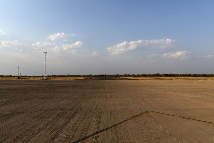Scenic view of runway at airport against sky