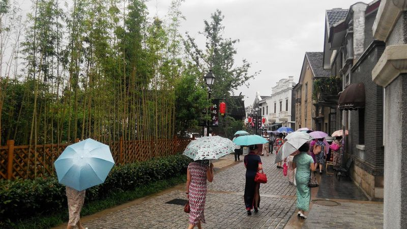 Nice ladies wearing qipao a classical Chinese dress on a rainy day are walking along an ancient street in Suzhou. Feel The Journey 43golden Moment