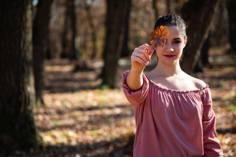 Portrait of young woman holding leaf