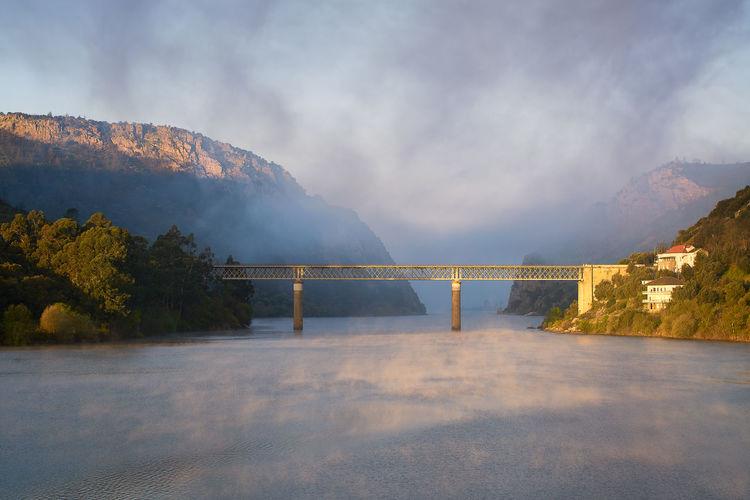 Scenic view of bridge over lake against sky