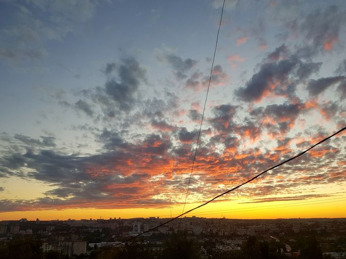 Low angle view of silhouette cables against sky during sunset