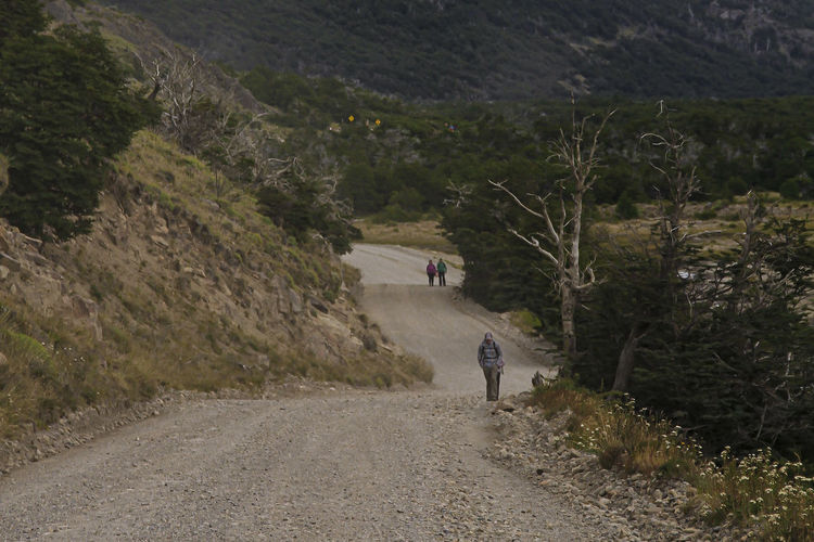 Rear view of people walking on road by mountain