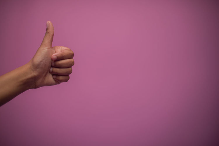 Close-up of person giving thumbs up against pink background