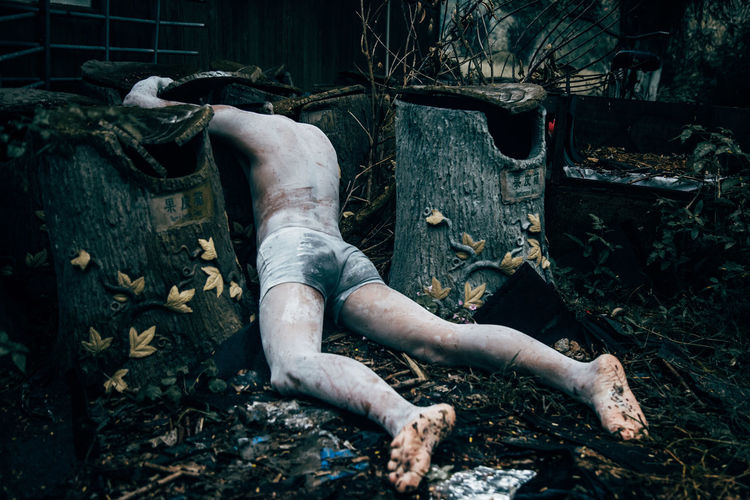 Rear view of hopeless shirtless man lying down by abandoned containers