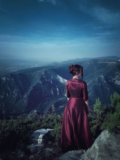 Rear view of woman standing on cliff against sky