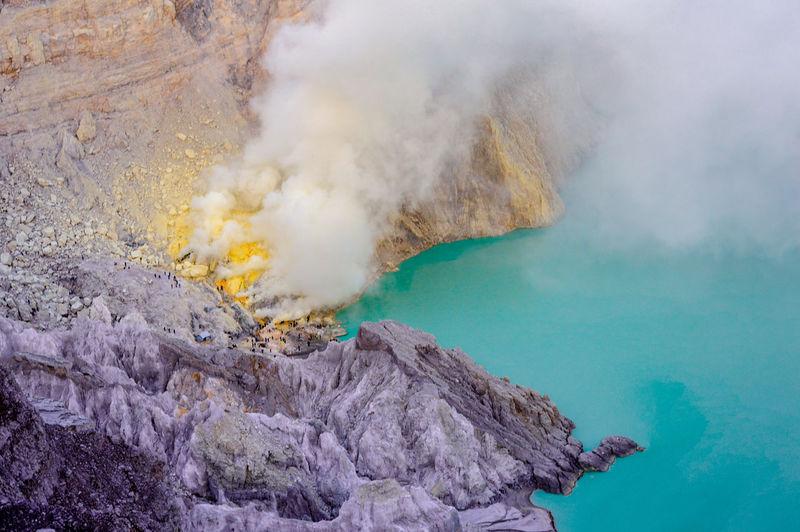 High angle view of smoke emitting from volcanic mountain