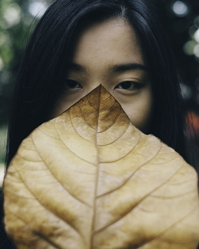 Portrait Of Young Woman Hiding Face With Autumn Leaf
