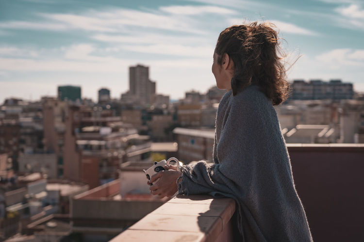Side view of woman looking at cityscape while standing on terrace