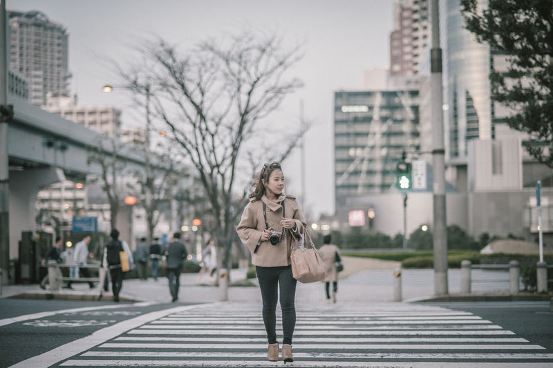 Full length of woman walking on street in city