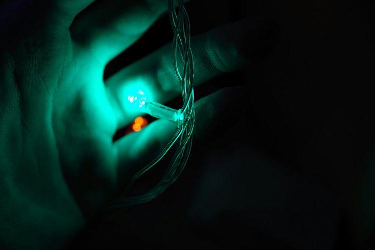 Close-up of hand on illuminated light