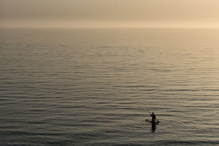 High angle view of silhouette person in sea