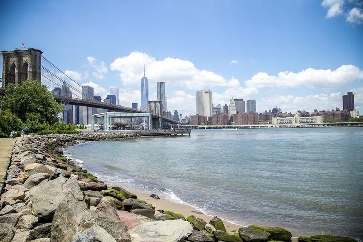 East River By Brooklyn Bridge Against Sky In City